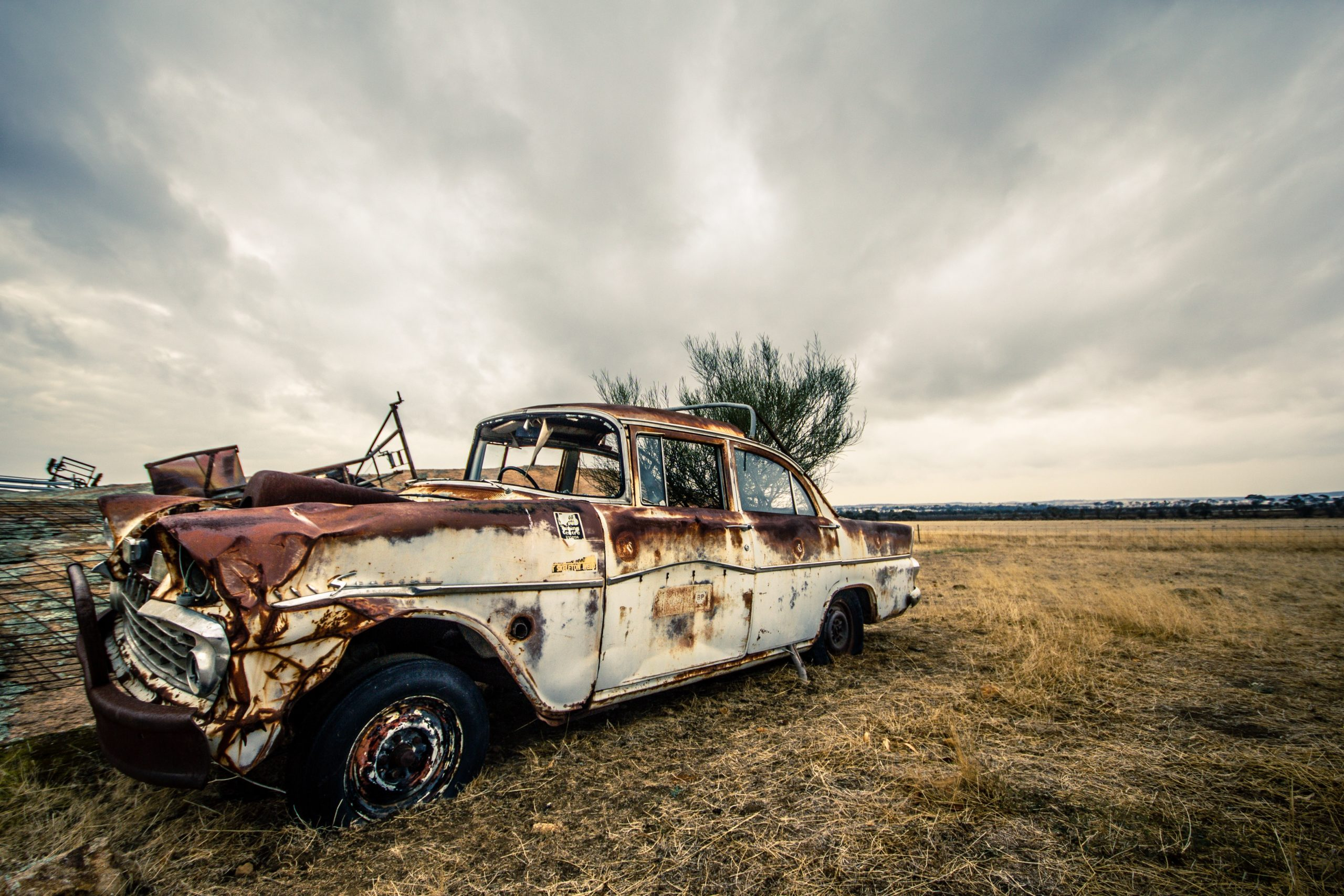 rusty damaged vintage car in field cloudy sky